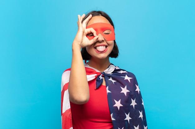 Молодая латинская женщина счастливо улыбается с забавным лицом, шутит и смотрит в глазок