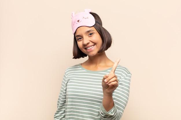 誇らしげに自信を持って笑顔の若いラテン女性が、リーダーのように、勝ち誇ってナンバーワンのポーズをとっています