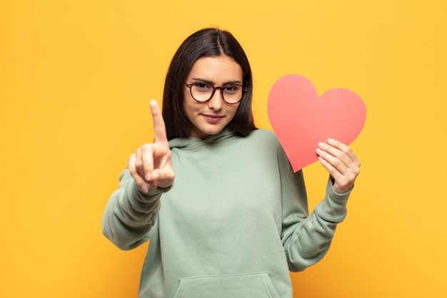 誇らしげに自信を持って笑顔の若いラテン女性が、リーダーのように感じて、勝ち誇ってナンバーワンのポーズをとっています