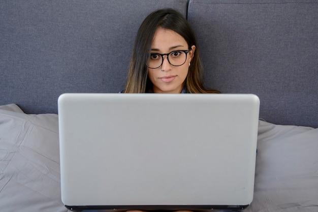 彼女のラップトップで自宅で仕事をしながら笑っている若いラテン女性