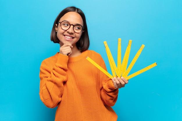 Молодая латинская женщина улыбается со счастливым, уверенным выражением лица, положив руку на подбородок, задается вопросом и смотрит в сторону