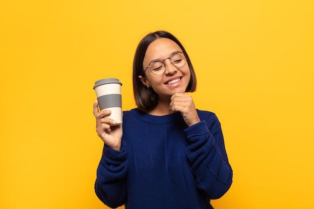 Молодая латинская женщина улыбается со счастливым, уверенным выражением лица, положив руку на подбородок