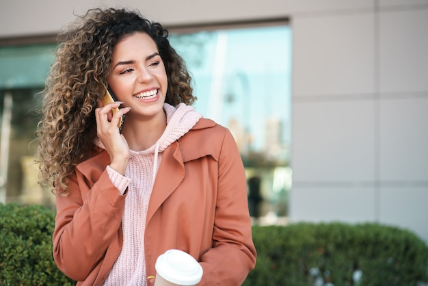 通りの屋外のベンチに座って電話で話している若いラテン女性。アーバンコンセプト。