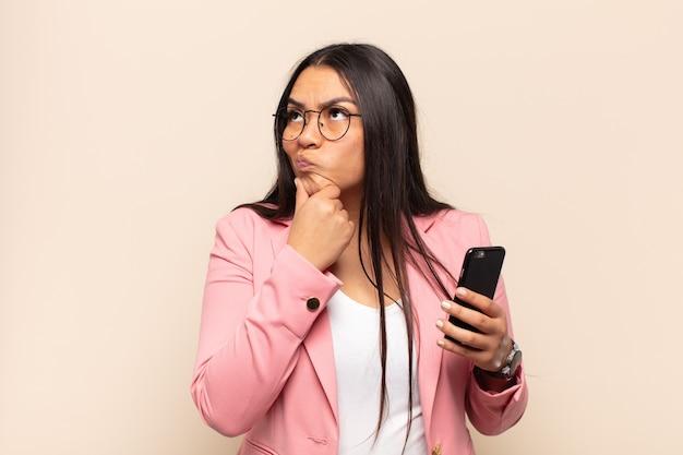 Молодая латинская женщина думает, сомневается и сбивается с толку, с разными вариантами, задается вопросом, какое решение принять