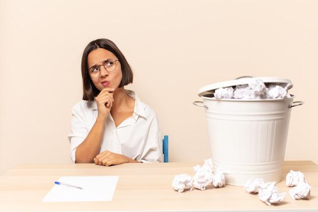 Молодая латинская женщина думает, чувствует себя сомневающейся и сбитой с толку, с разными вариантами, задаваясь вопросом, какое решение принять