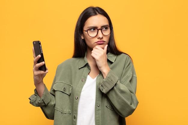 젊은 라틴 여성은 생각하고 의심스럽고 혼란스러워하며 다양한 선택을 하며 어떤 결정을 내려야 할지 궁금해합니다.