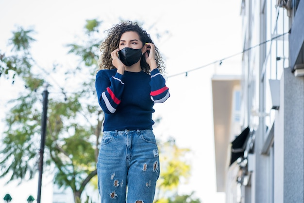 通りの屋外で電話で話している間フェイスマスクを使用して若いラテン女性。新しい通常のライフスタイル。アーバンコンセプト。