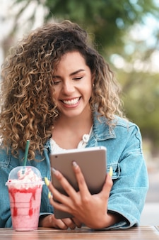 Young latin woman using a digital tablet while drinking a cold drink beverage at a coffee shop outdoors on the street.
