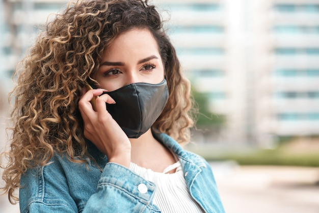 Young latin woman using a face mask while talking on the phone outdoors in the street. new normal lifestyle. urban concept.