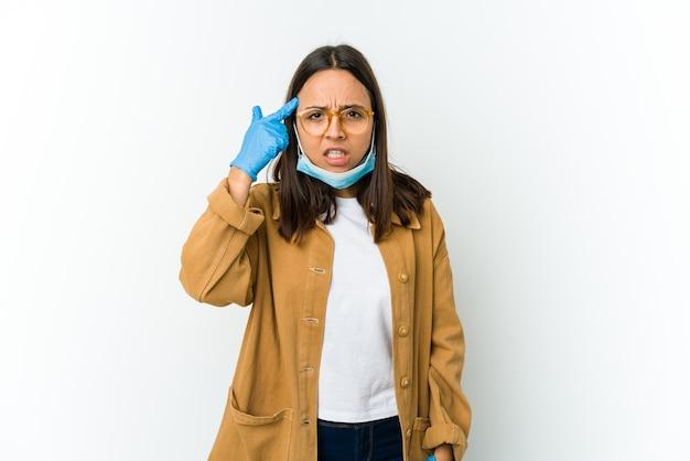 Молодая латинская женщина в маске для защиты от covid изолирована на белом фоне, показывая жест разочарования указательным пальцем.