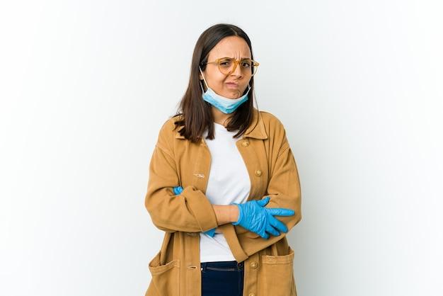 Молодая латинская женщина в маске для защиты от covid, изолированных на белом фоне, недовольна, глядя в камеру с саркастическим выражением лица.