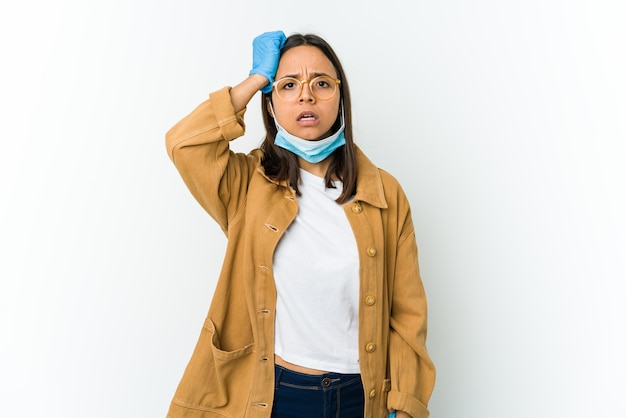 흰색에 고립 된 covid에서 보호하기 위해 마스크를 쓰고 젊은 라틴 여자 피곤하고 매우 졸린 유지 손을 머리에.