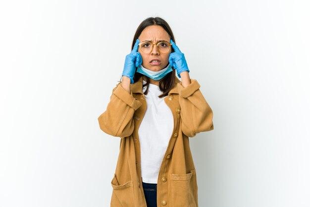 Молодая латинская женщина в маске для защиты от covid, изолированная на белой стене, сосредоточилась на задаче, держа указательные пальцы указывая головой.