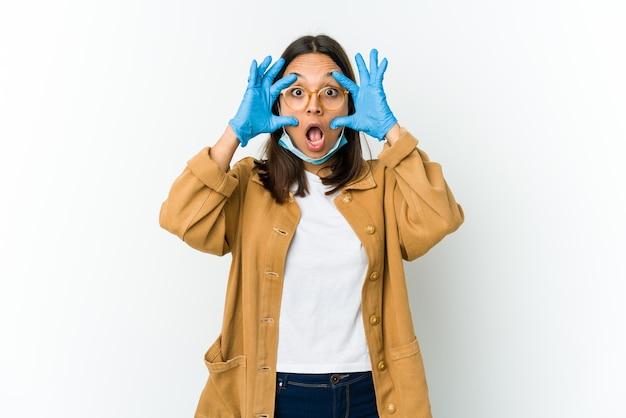 Молодая латинская женщина в маске для защиты от covid изолирована на белой стене, держа глаза открытыми, чтобы найти возможность успеха