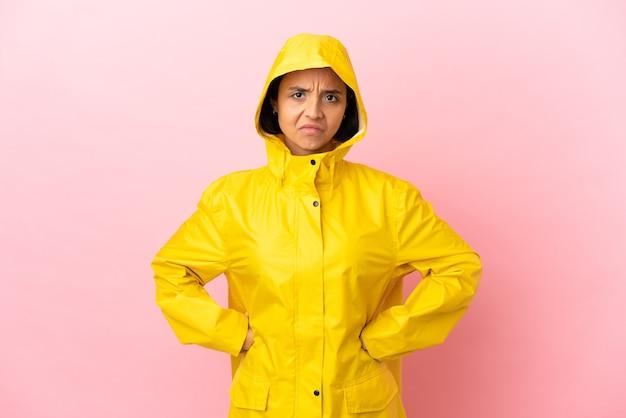 Молодая латинская женщина в непромокаемом пальто на изолированном фоне сердится