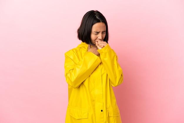 격리된 배경 위에 방수 코트를 입은 젊은 라틴 여성이 기침을 많이 합니다