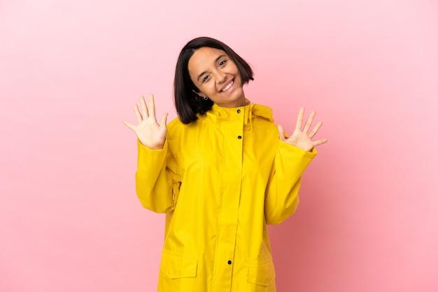 指で10を数える孤立した背景の上に防雨コートを着ている若いラテン女性