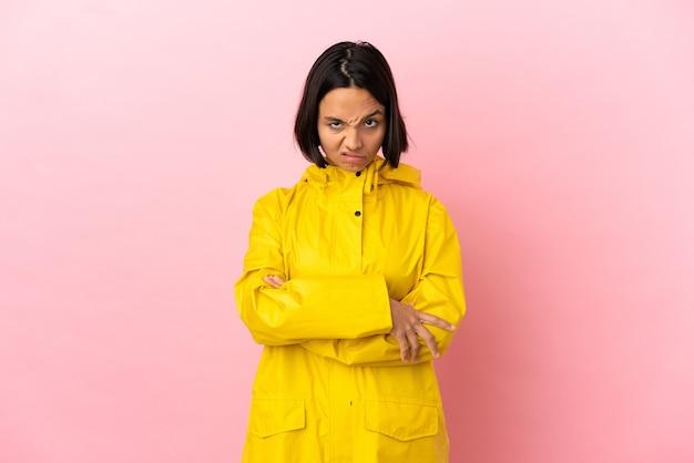 動揺を感じて孤立した背景の上に防雨コートを着ている若いラテン女性