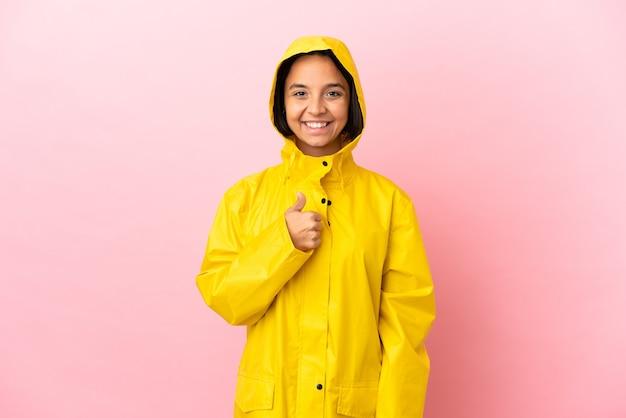 親指を立てるジェスチャーを与える孤立した背景の上に防雨コートを着ている若いラテン女性