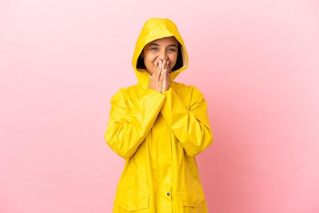 孤立した背景の上に防雨コートを着ている若いラテン女性幸せと笑顔の手で口を覆う