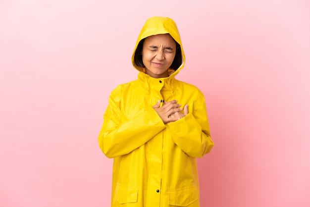 心の痛みを持っている孤立した背景の上に防雨コートを着ている若いラテン女性