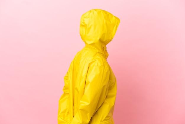 後ろの位置で孤立した背景の上に防雨コートを着て、振り返って若いラテン女性