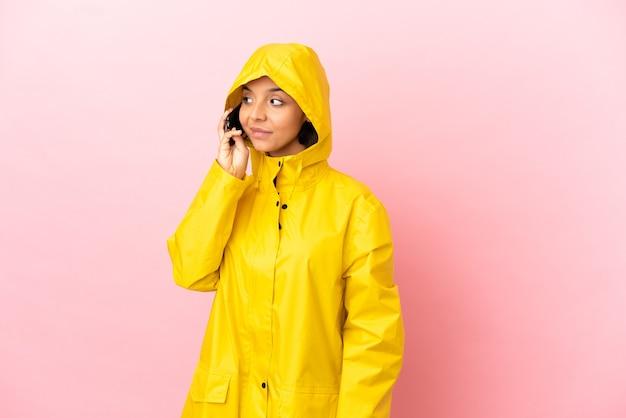 誰かと携帯電話との会話を維持している孤立した背景の上に防雨コートを着ている若いラテン女性