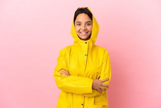 Молодая латинская женщина в непромокаемом пальто на изолированном фоне, скрестив руки на груди