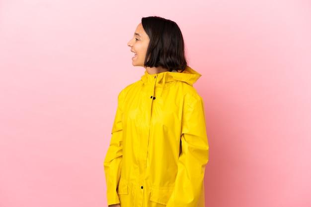 외진 배경 위에 방수 코트를 입고 옆으로 웃고 있는 젊은 라틴 여성