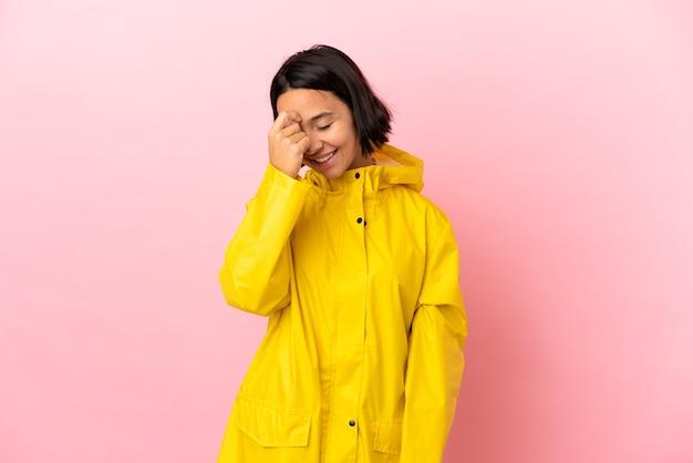 외진 배경 위에 방수 코트를 입고 웃고 있는 젊은 라틴 여성