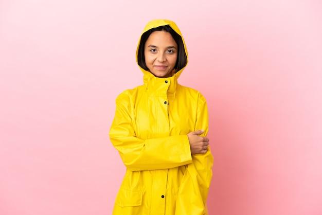 笑っている孤立した背景の上に防雨コートを着ている若いラテン女性