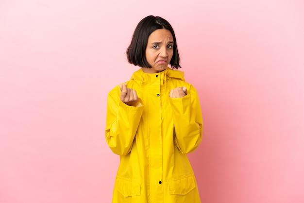 Молодая латинская женщина в непромокаемом пальто на изолированном фоне делает денежный жест, но разрушена