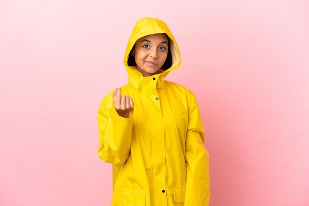 Молодая латинская женщина в непромокаемом пальто на изолированном фоне делает денежный жест