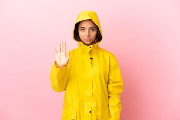 외진 배경 위에 방수 코트를 입고 정지 제스처를 취하는 젊은 라틴 여성