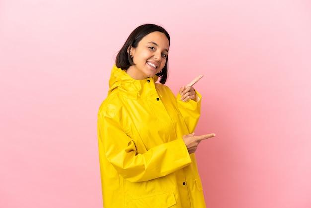 Молодая латинская женщина в непромокаемом пальто на изолированном фоне, указывая пальцем в сторону и представляя продукт