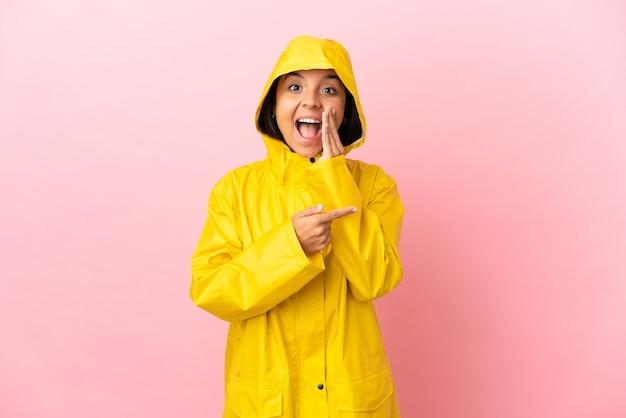 製品を提示し、何かをささやくために側面を指している孤立した背景の上に防雨コートを着ている若いラテン女性