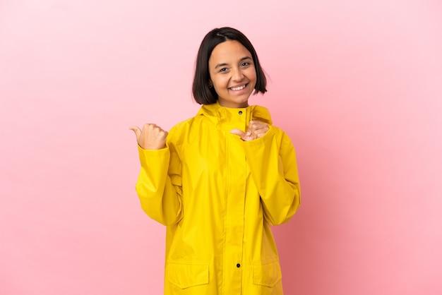 製品を提示する側を指している孤立した背景の上に防雨コートを着ている若いラテン女性