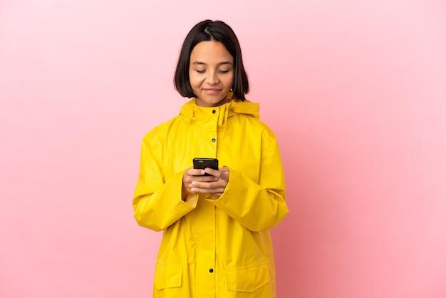 携帯電話でメッセージを送信する孤立した背景の上に防雨コートを着ている若いラテン女性