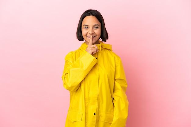 격리된 배경 위에 방수 코트를 입은 젊은 라틴 여성은 입에 손가락을 넣는 침묵 제스처의 표시를 보여줍니다.