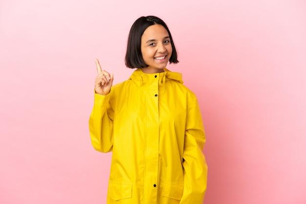 孤立した背景の上に防雨コートを着て、最高の兆候を示して指を持ち上げる若いラテン女性