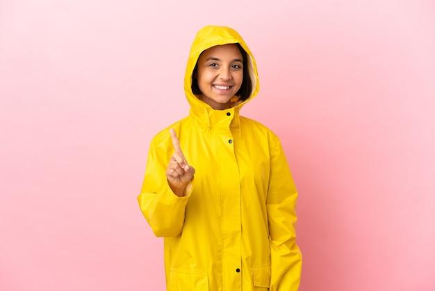 指を見せて持ち上げる孤立した背景の上に防雨コートを着ている若いラテン女性