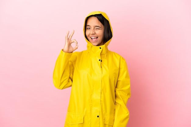 Молодая латинская женщина в непромокаемом пальто на изолированном фоне показывает пальцами знак ок