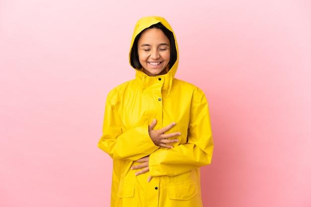 외진 배경 위에 방수 코트를 입은 젊은 라틴 여성이 많이 웃고 있다