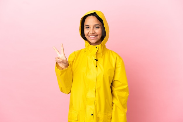 Молодая латинская женщина в непромокаемом пальто на изолированном фоне улыбается и показывает знак победы