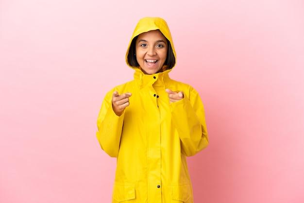 孤立した背景の上に防雨コートを着ている若いラテン女性は驚いて正面を指しています