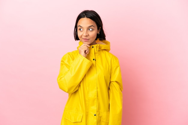 見上げながらアイデアを考えて孤立した背景の上に防雨コートを着ている若いラテン女性