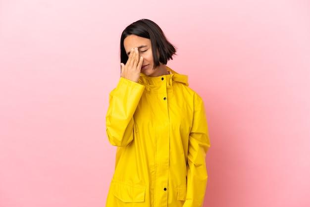 頭痛のある孤立した背景の上に防雨コートを着ている若いラテン女性