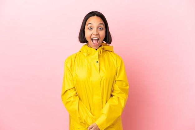 驚きの表情で孤立した背景の上に防雨コートを着ている若いラテン女性
