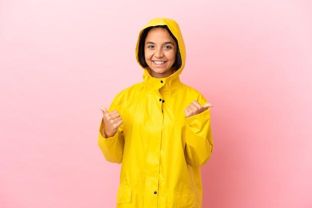 Молодая латинская женщина в непромокаемом пальто на изолированном фоне с пальцами вверх жестом и улыбкой