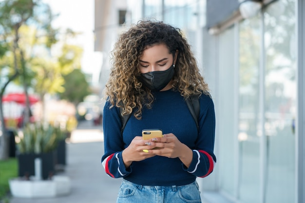 Young latin woman wearing a face mask while using her mobile phone outdoors in the street. new normal lifestyle concept. urban concept.